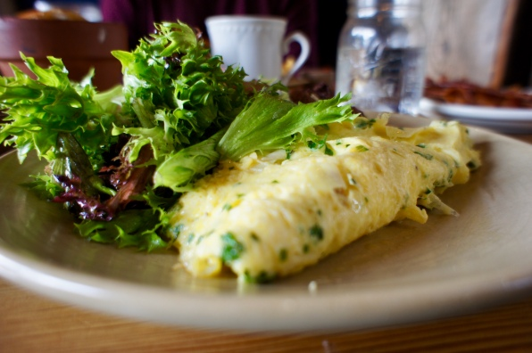 Omelette with gruyere, leeks, potatoes and greens with a side of bacon